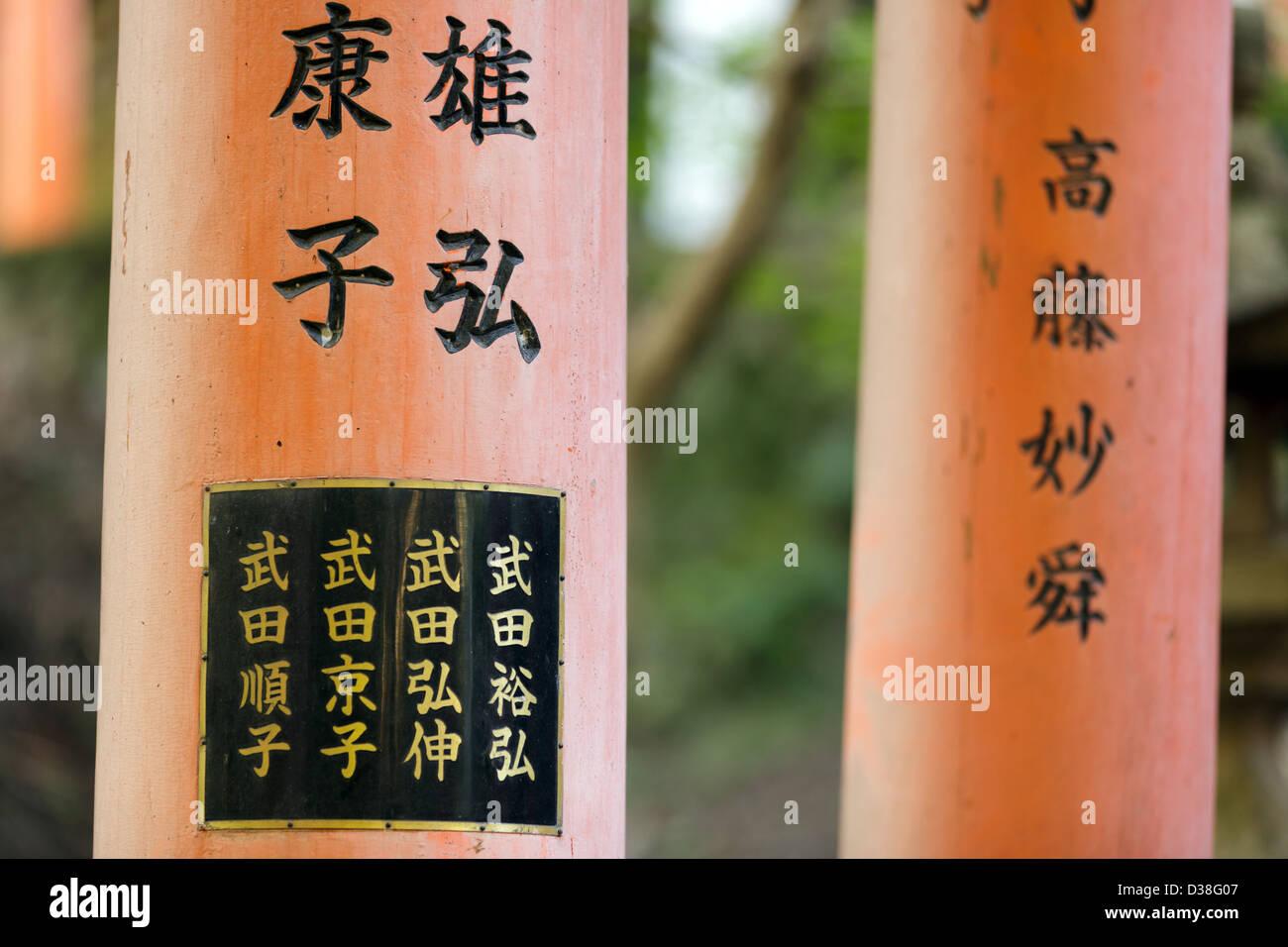 Kanji writings on fushimi Inari shrine torii in Kyoto, Japan - Stock Image