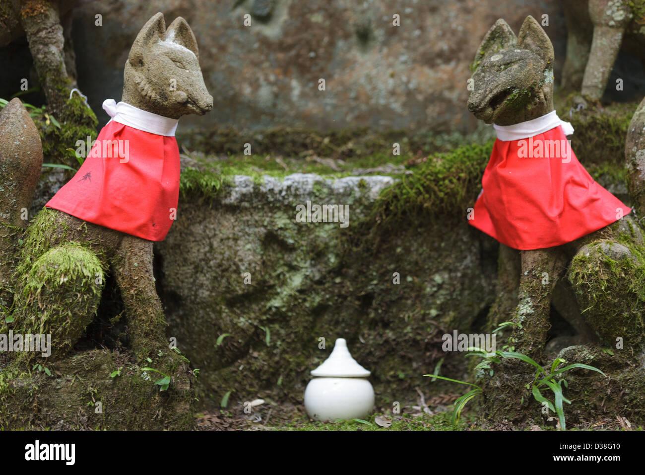 small god fox statue and tombstone in fushimi inari shrine near Kyoto, Japan - Stock Image