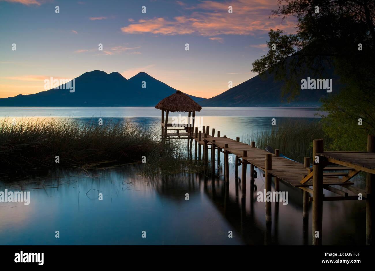 Wooden pier in still lake - Stock Image
