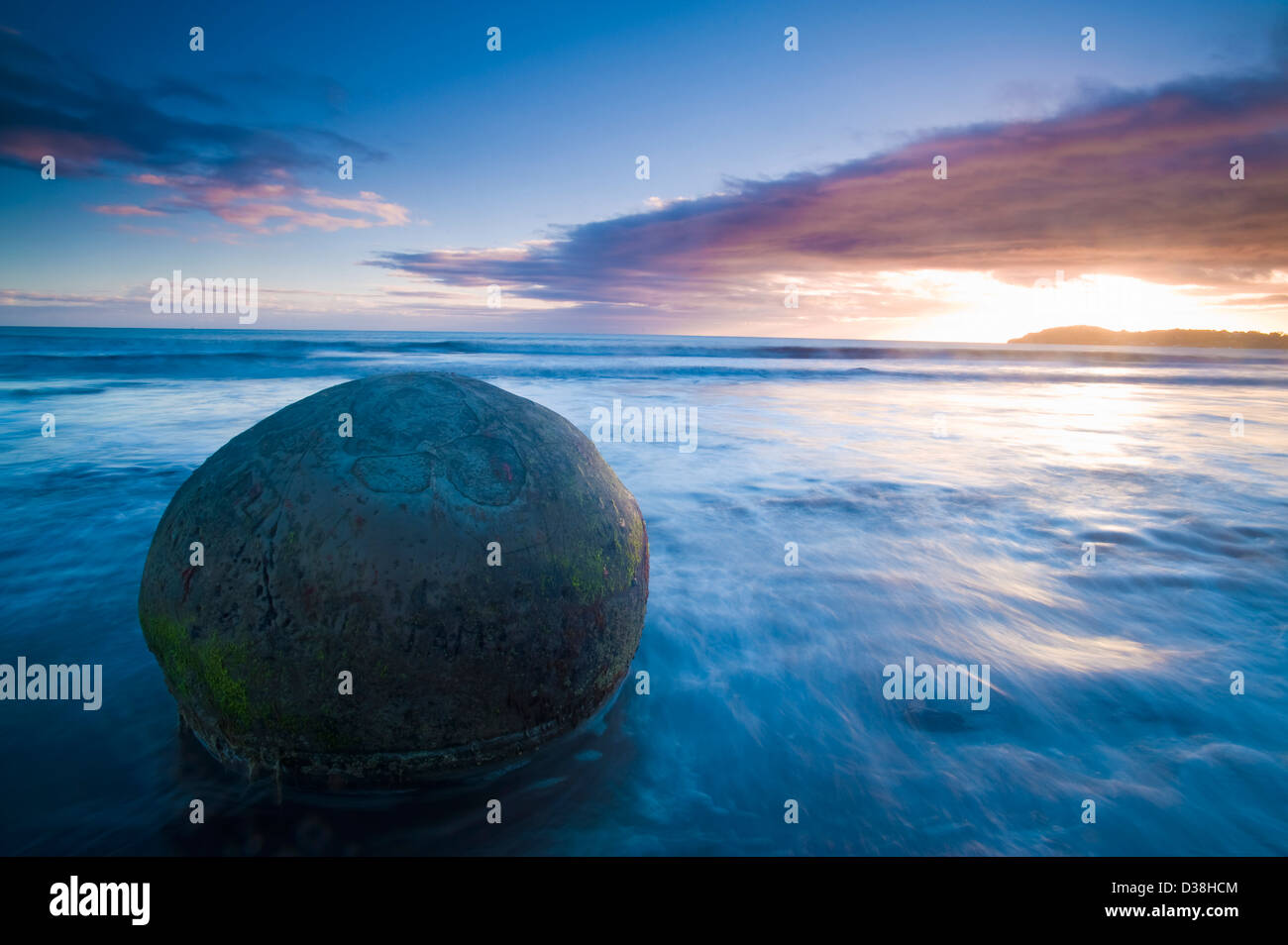 Waves washing over rock on beach - Stock Image