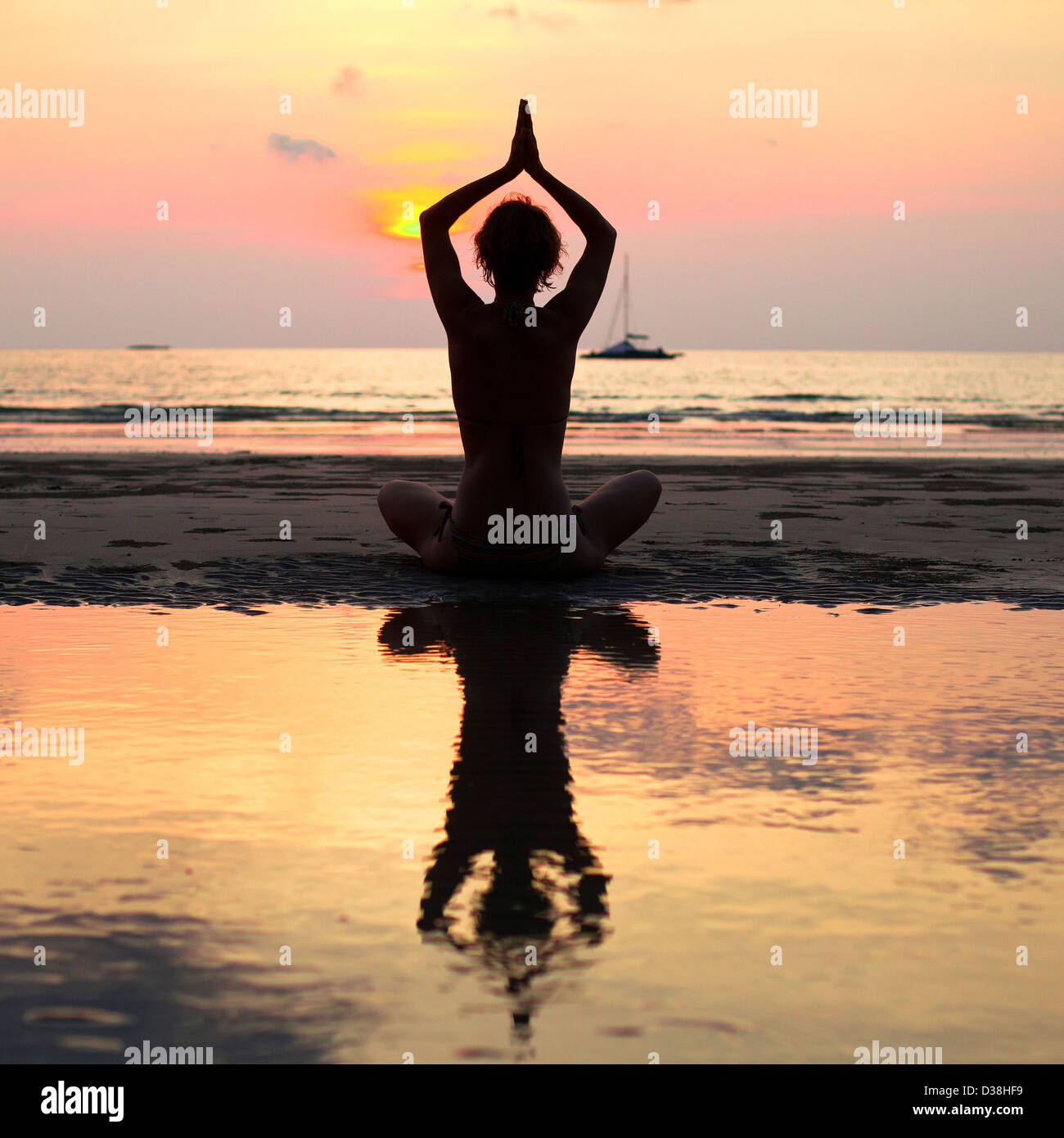 Yoga woman sitting in lotus pose on the beach during sunset, with reflection in water - Stock Image