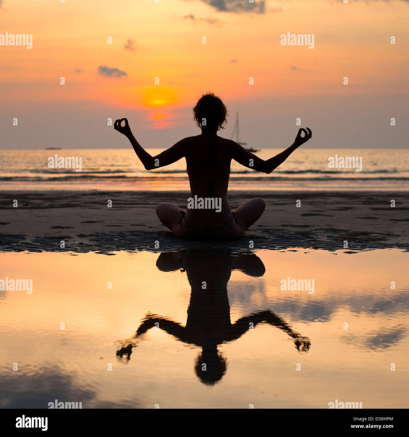 Yoga woman sitting in lotus pose on the beach during sunset, with reflection in water. - Stock Image