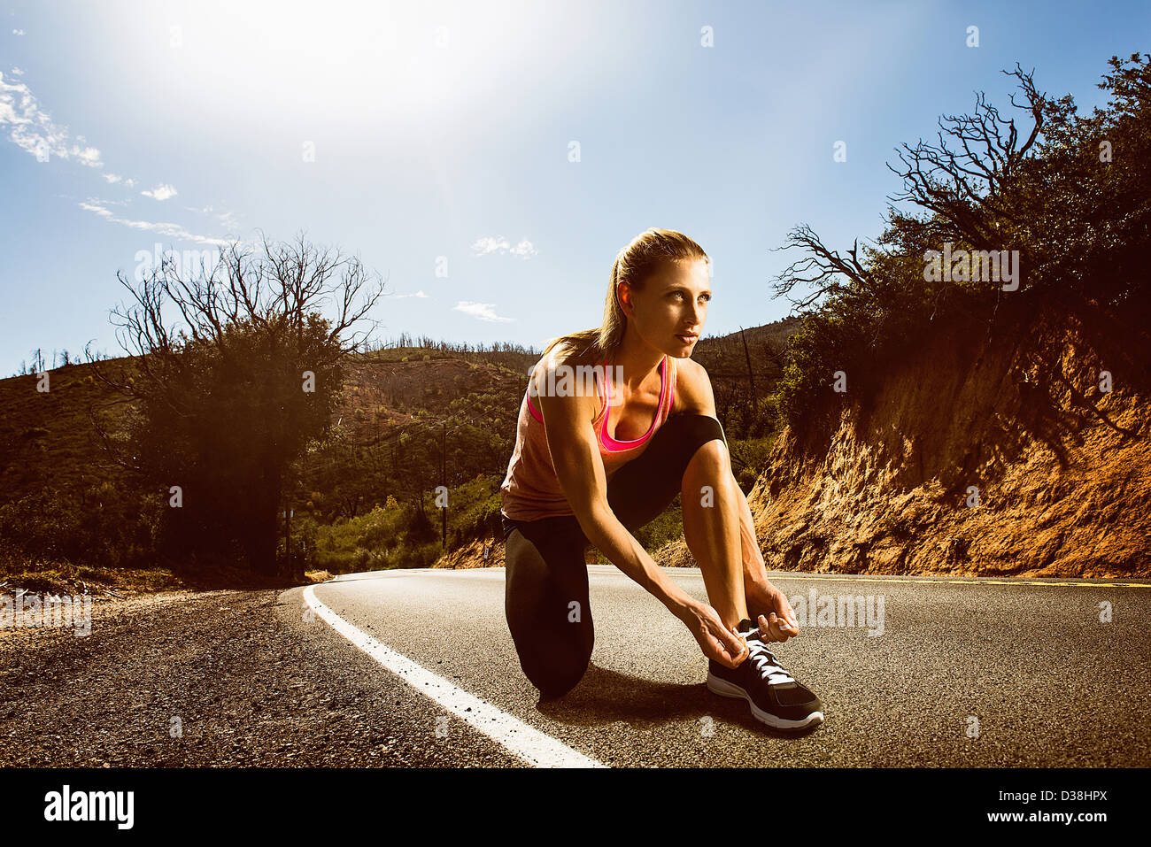 Runner lacing up shoes on rural road - Stock Image