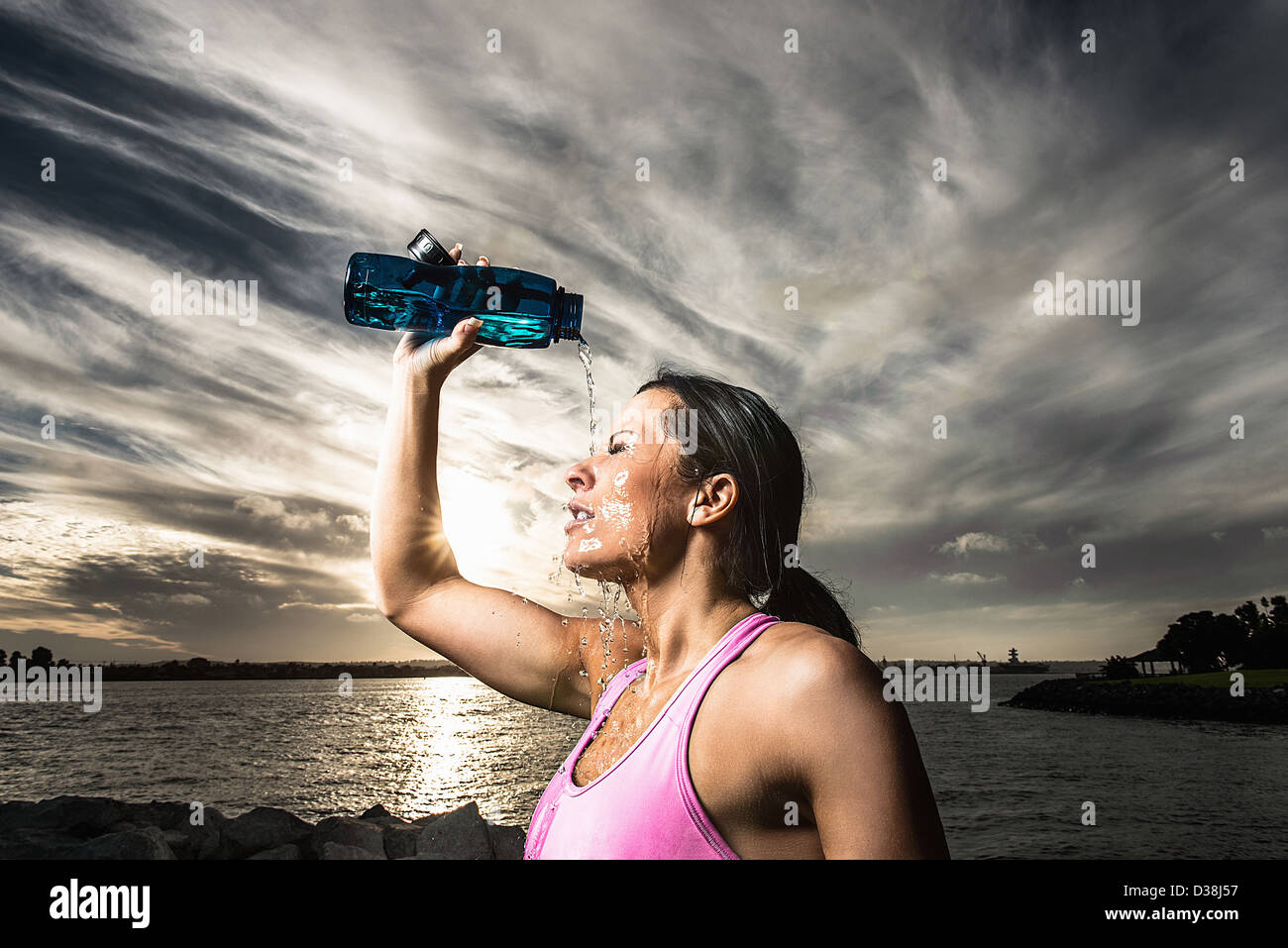 Runner pouring water on herself - Stock Image