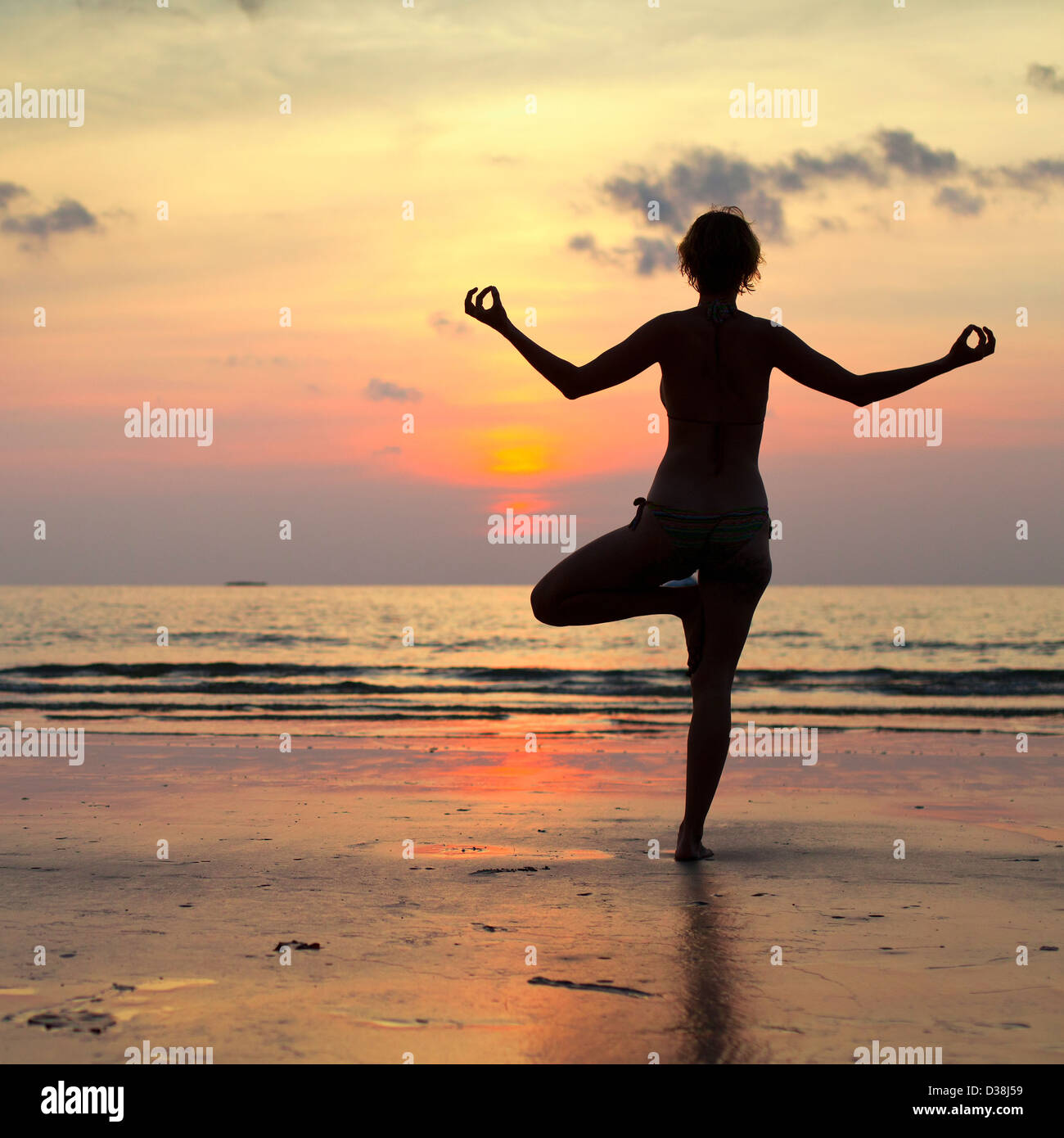 Yoga woman performs an exercise on the beach during sunset, with reflection in water - Stock Image