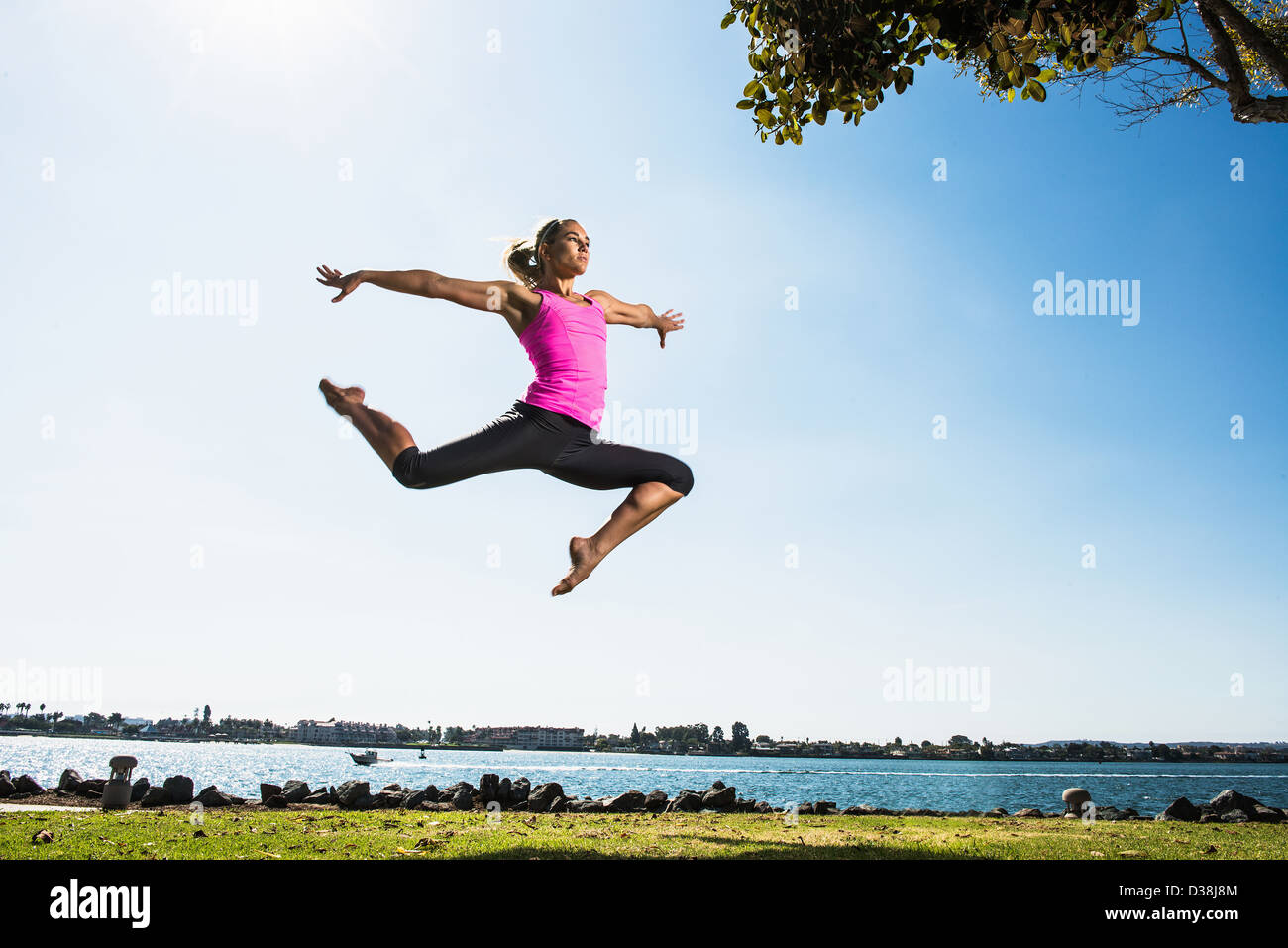 Woman leaping in park - Stock Image