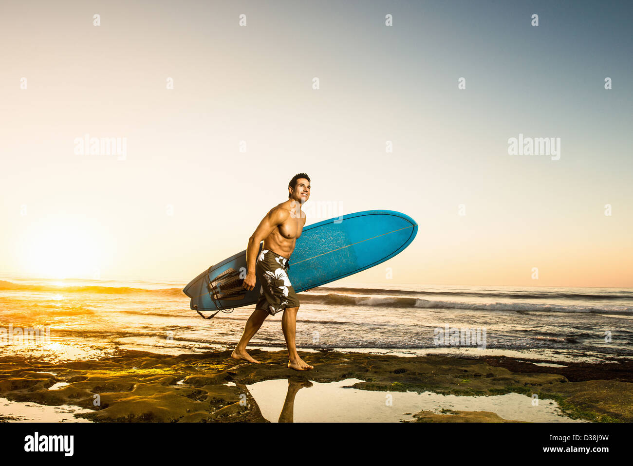 Man carrying surfboard on rocky beach - Stock Image