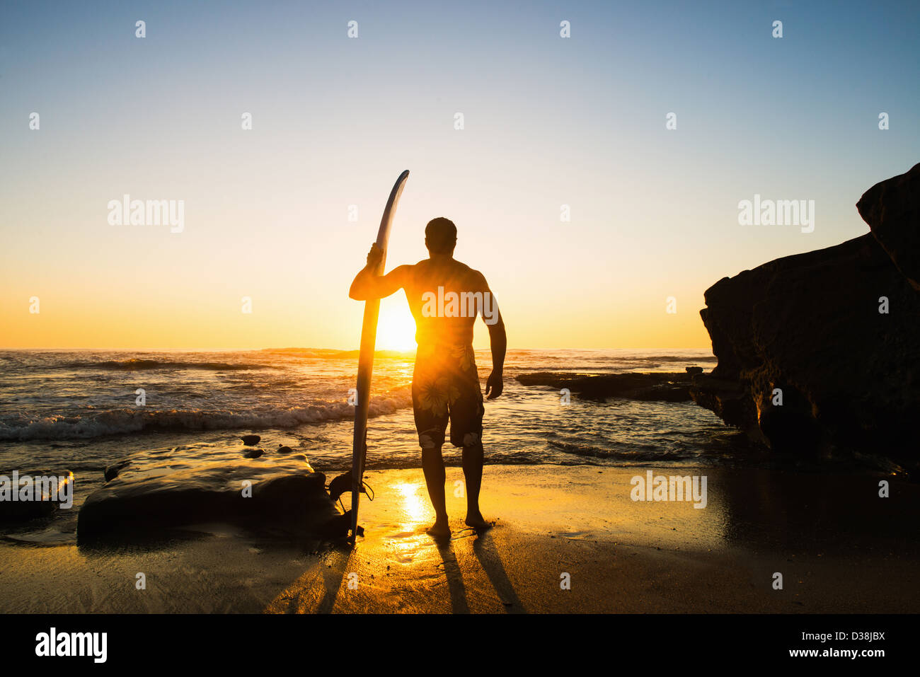 Man holding surfboard on rocky beach - Stock Image