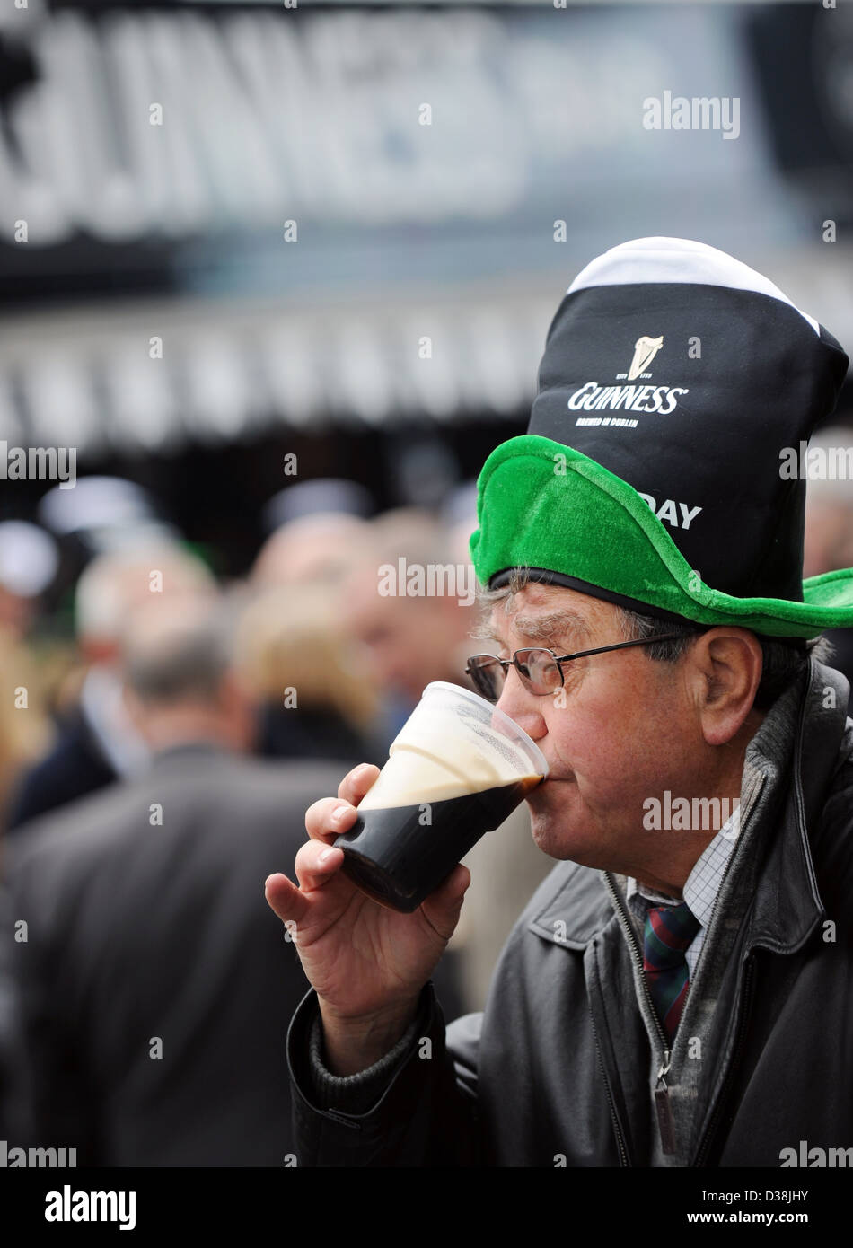 A man drinks a pint of Guinness on St. Patricks Day during the Cheltenham horse racing festival Stock Photo