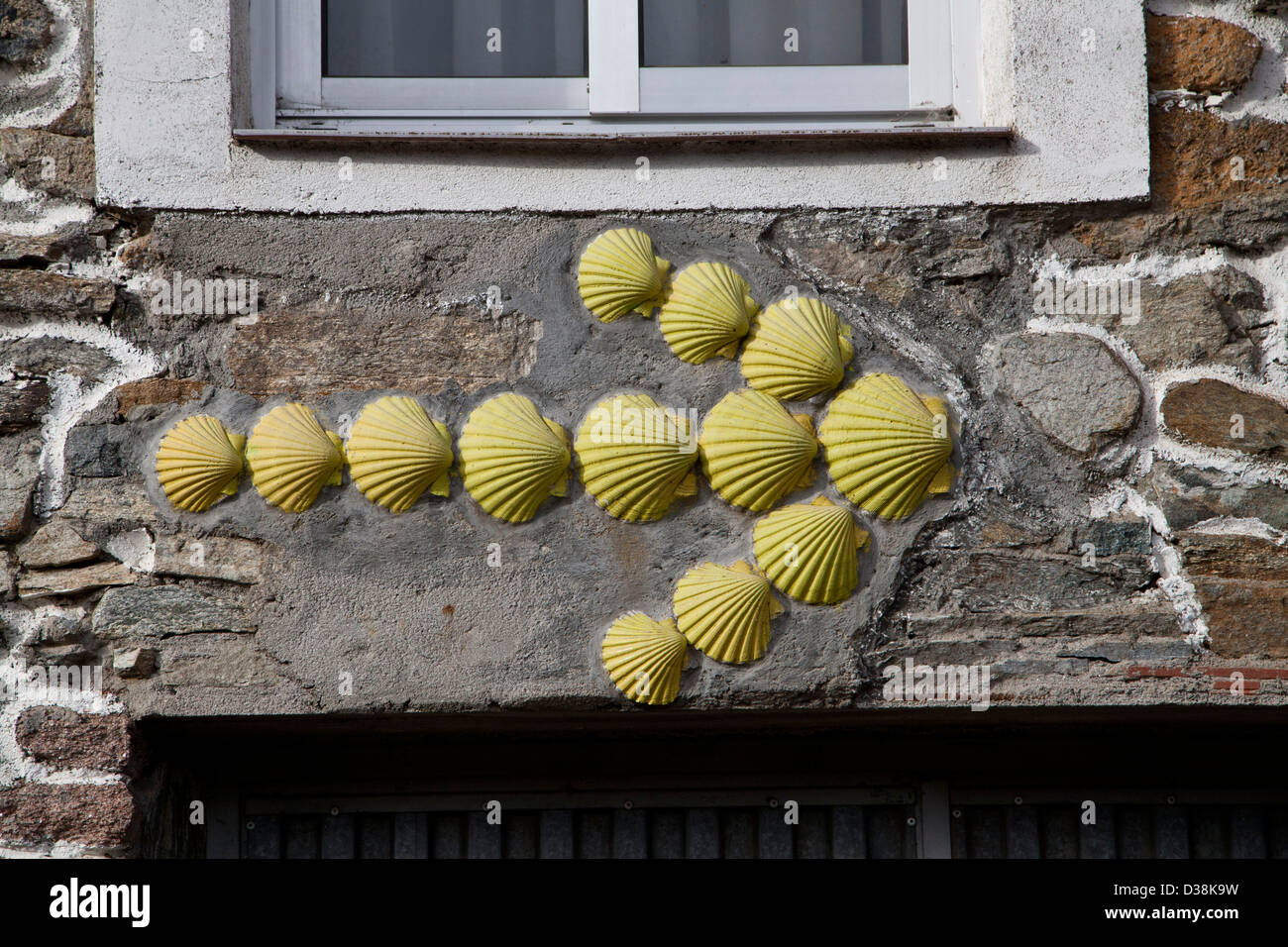 scallop shells shaped to form a yellow arrow, route marker for The Way of St. James, El Camino to Santiago de Compostela - Stock Image