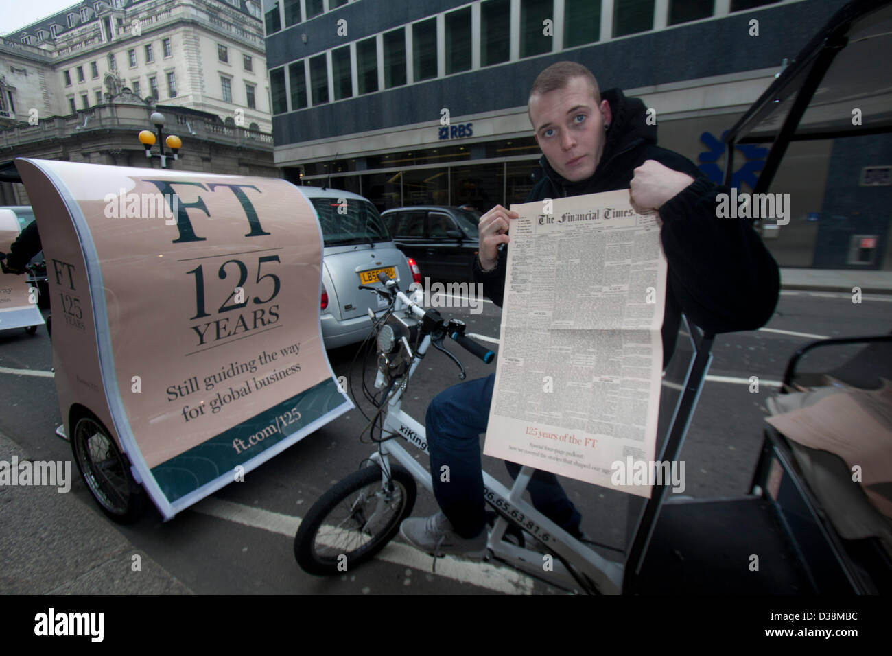 London, UK. 13th February 2013. A Newspaper vendor on  a rickshaw holds a copy of the first edition of the Financial - Stock Image