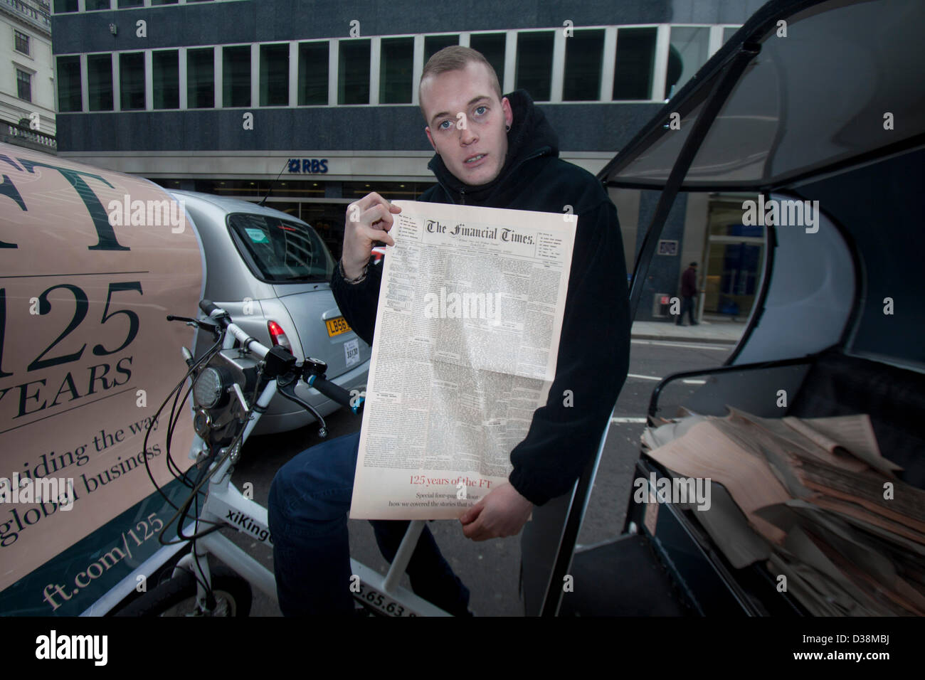London, UK. 13th February 2013. A newspaper vendor on a rickshaw holds a  copy of the first Financial Times edition - Stock Image