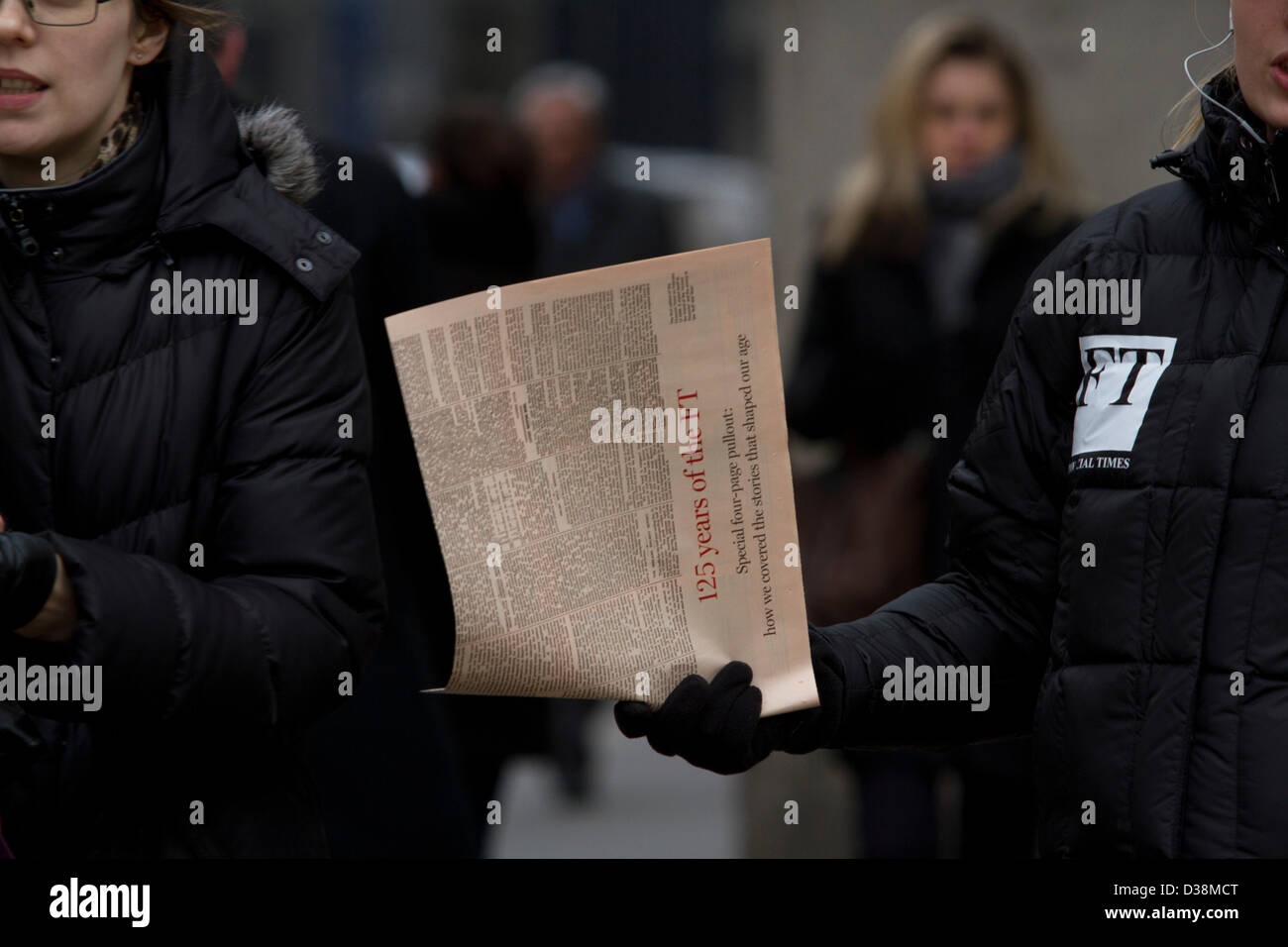London, UK. 13th February 2013. A Newspaper vendor distributes free copies of the first Financial Times in the city - Stock Image
