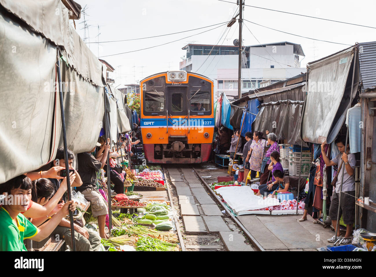 Train At Maeklong Railway Station And Market Thailand Stallholders Lifting Awnings To Allow Pass