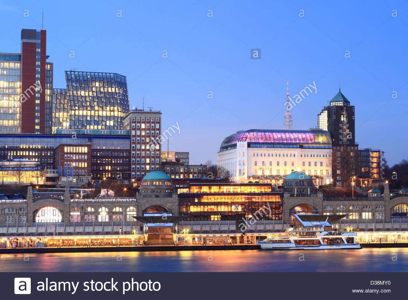 Urban waterfront lit up at night - Stock Image