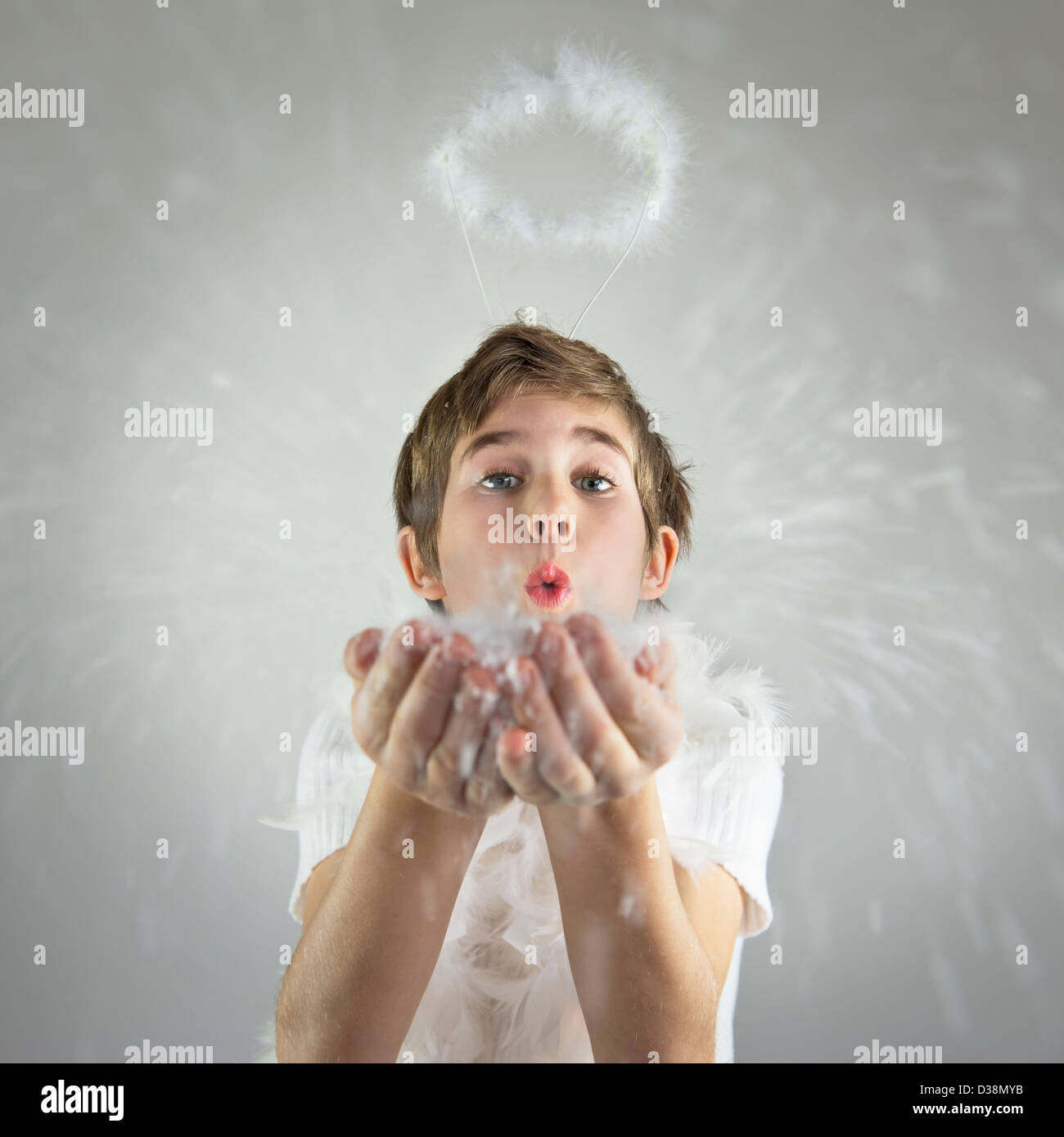 Boy with halo blowing handful of snow - Stock Image
