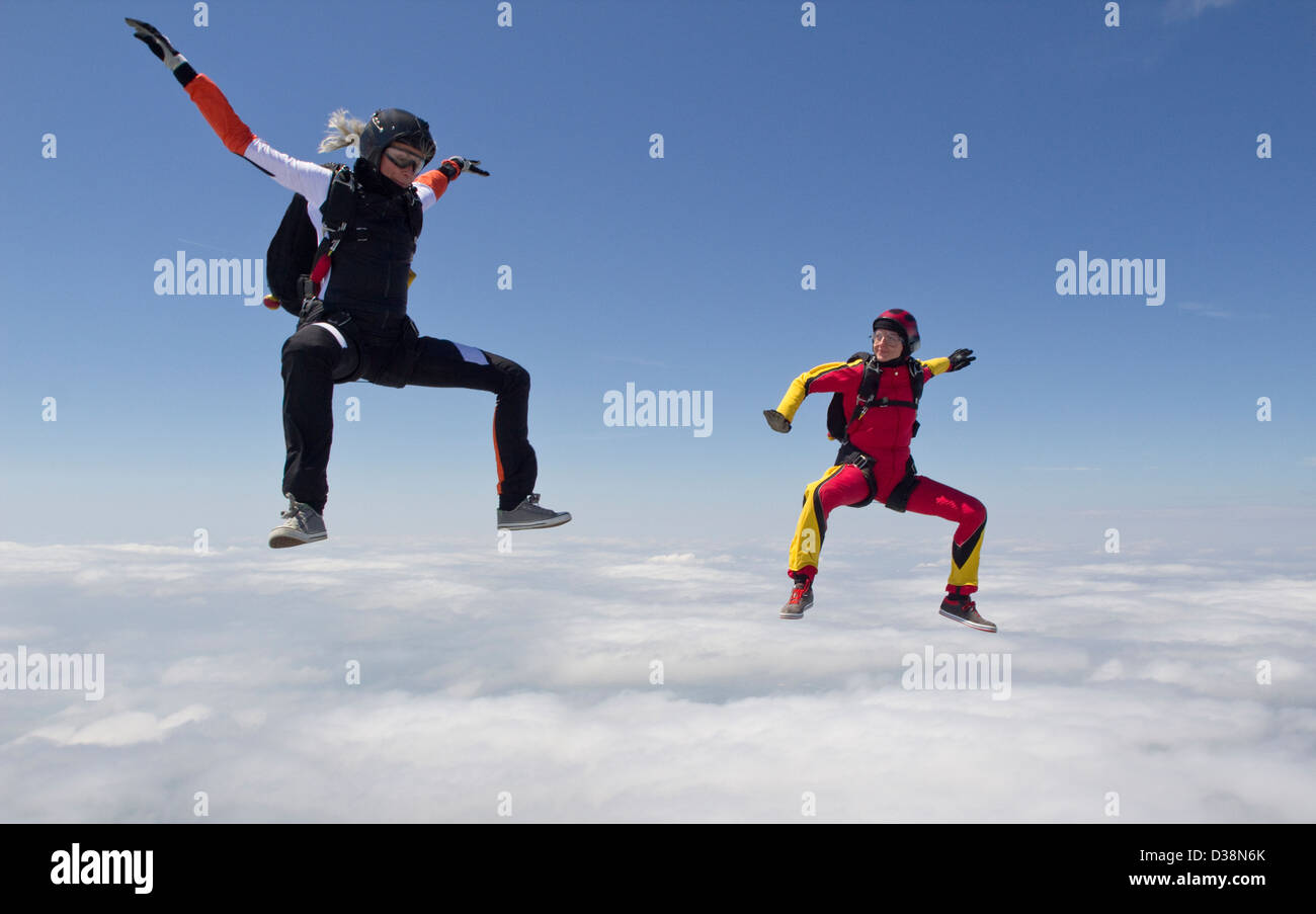 Women skydiving over clouds - Stock Image