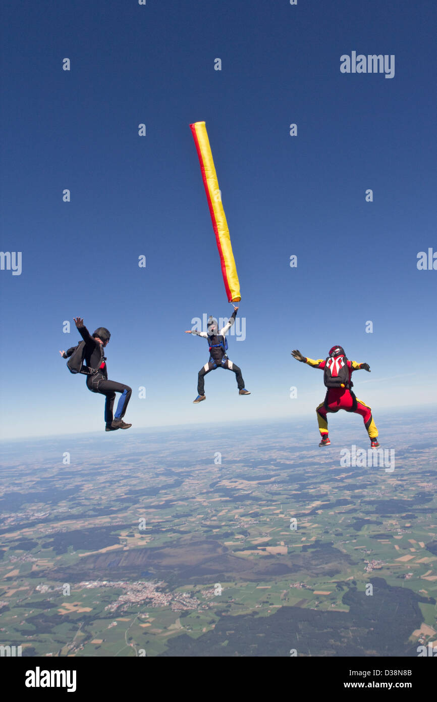People skydiving over rural landscape Stock Photo