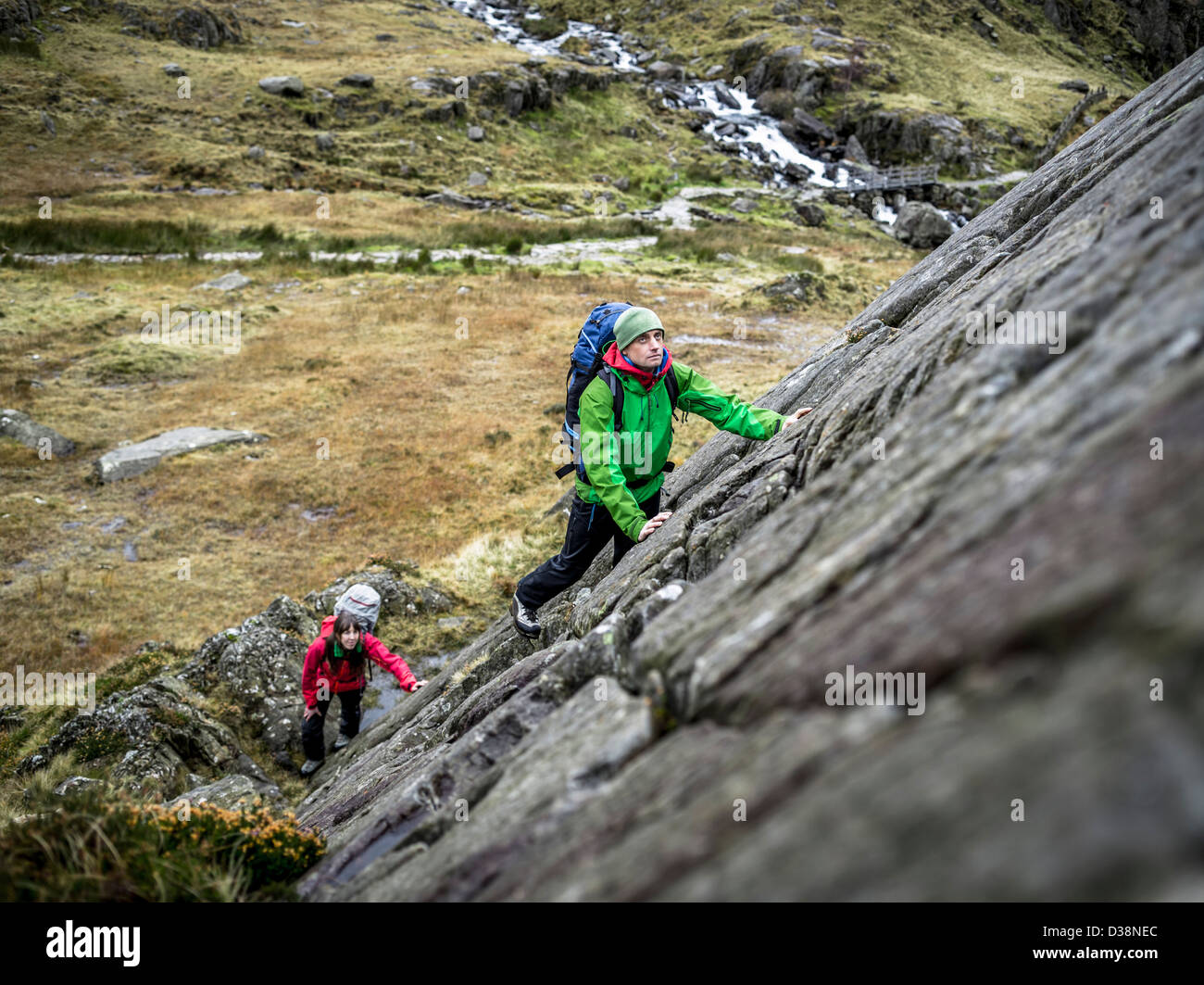 Hikers scaling steep rock face - Stock Image