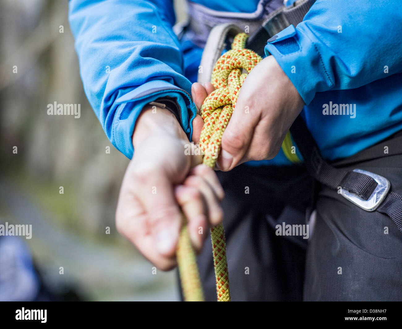 Rock climber tying rope - Stock Image