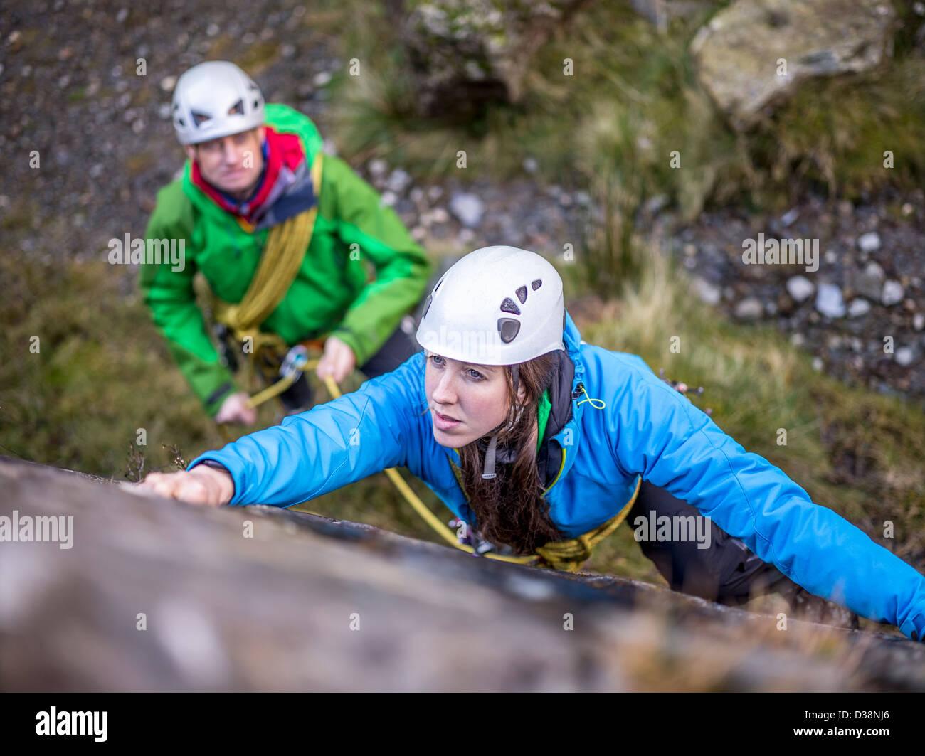 Rock climber scaling steep rock face - Stock Image