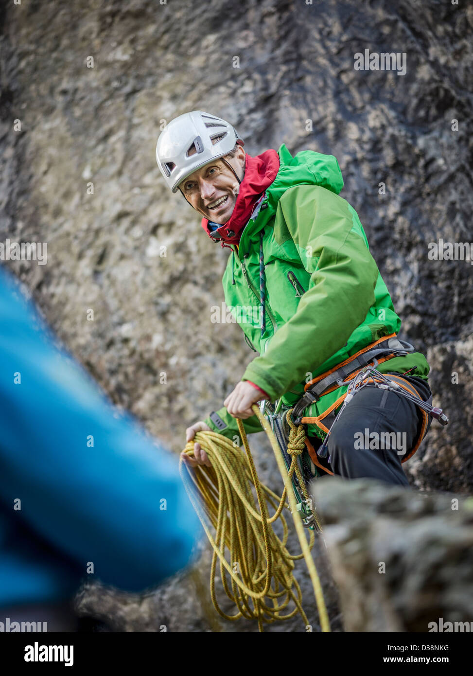 Rock climber pulling up rope - Stock Image