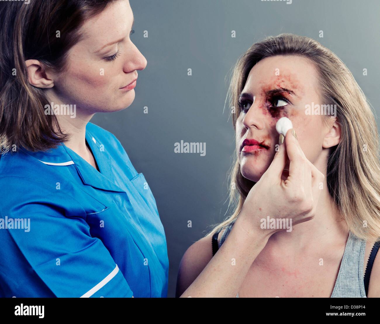 Nurse cleaning womans bruised face - Stock Image
