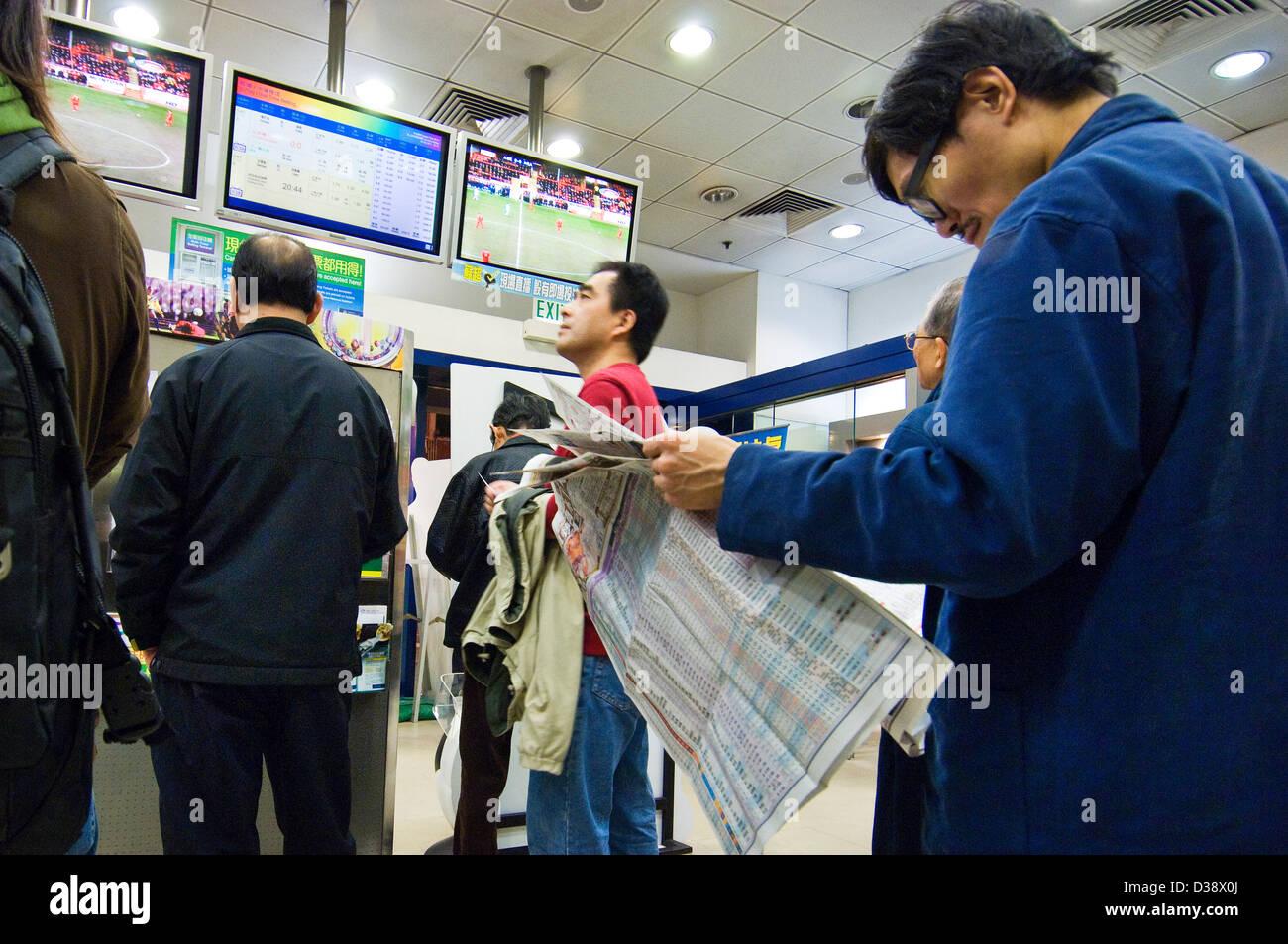 Gamblers in Hong Kong bet on English and European football and soccer games at a betting shop run by the Hong Kong - Stock Image