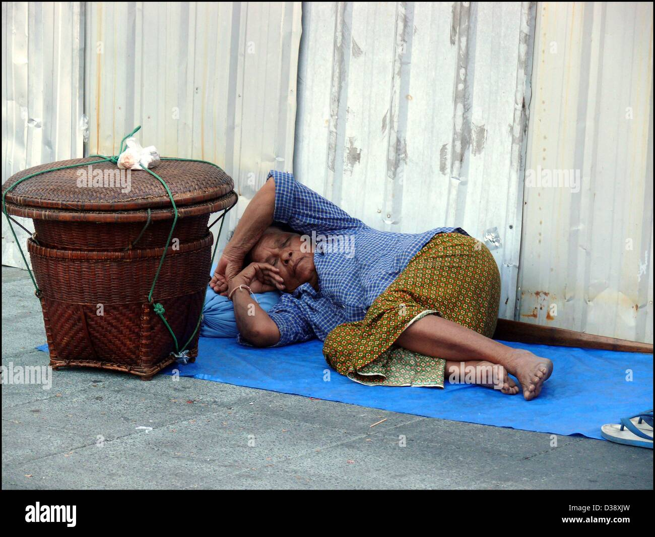 An old merchant woman schleeps on the street near the Tha Chang Pier in Bangkok - Stock Image