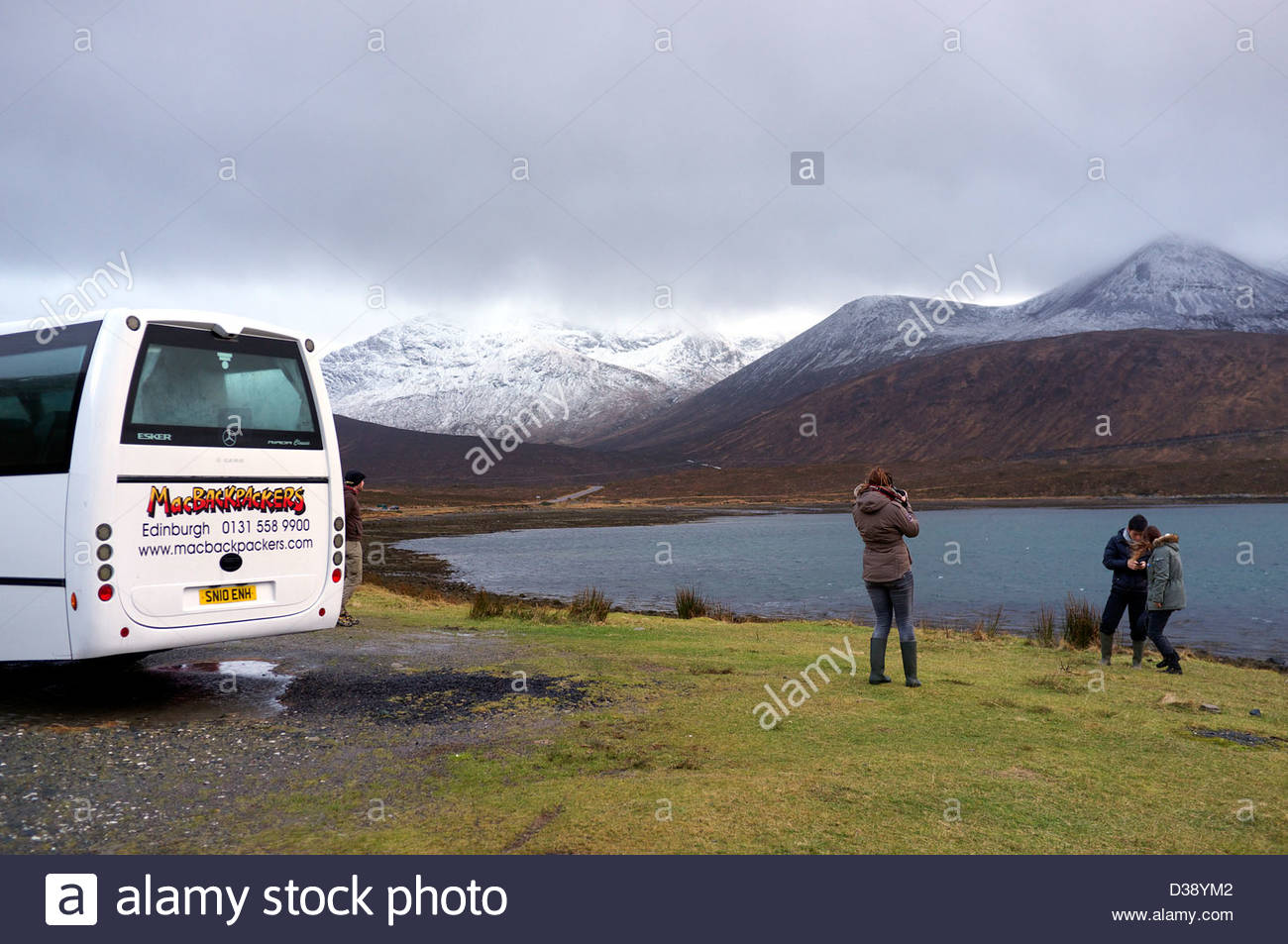 A backpackers tour bus stops off to allow the tourists to enjoy the wild Isle of Skye scenery, during winter 2013. - Stock Image