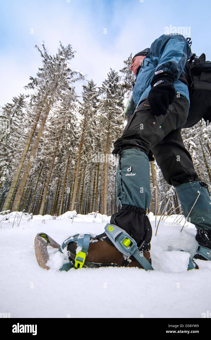 Close up of hiker wearing snowshoes on feet while snowshoeing in forest in deep powder snow in winter - Stock Image