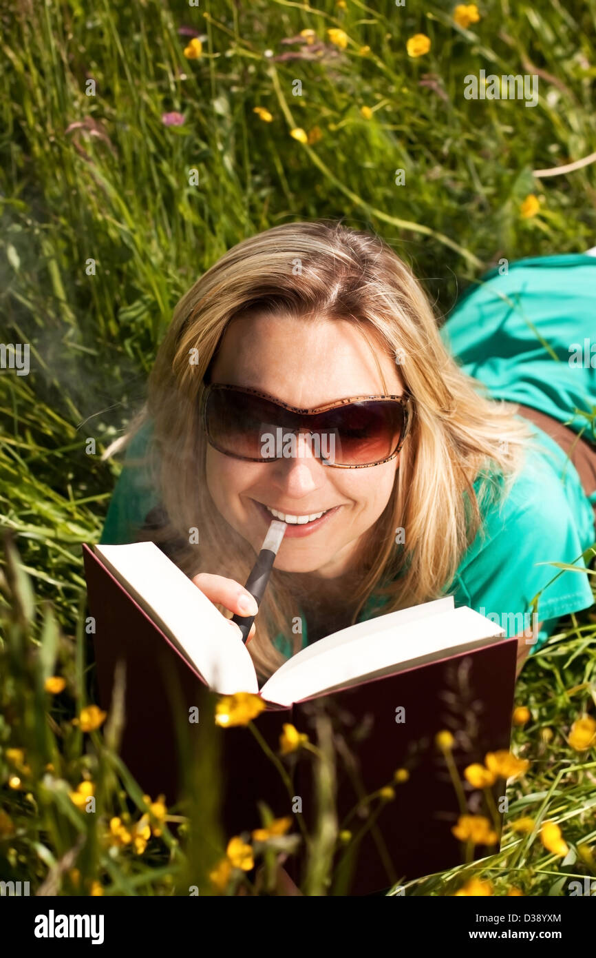 pretty woman reading , and evaporated to an electric cigarette - Stock Image