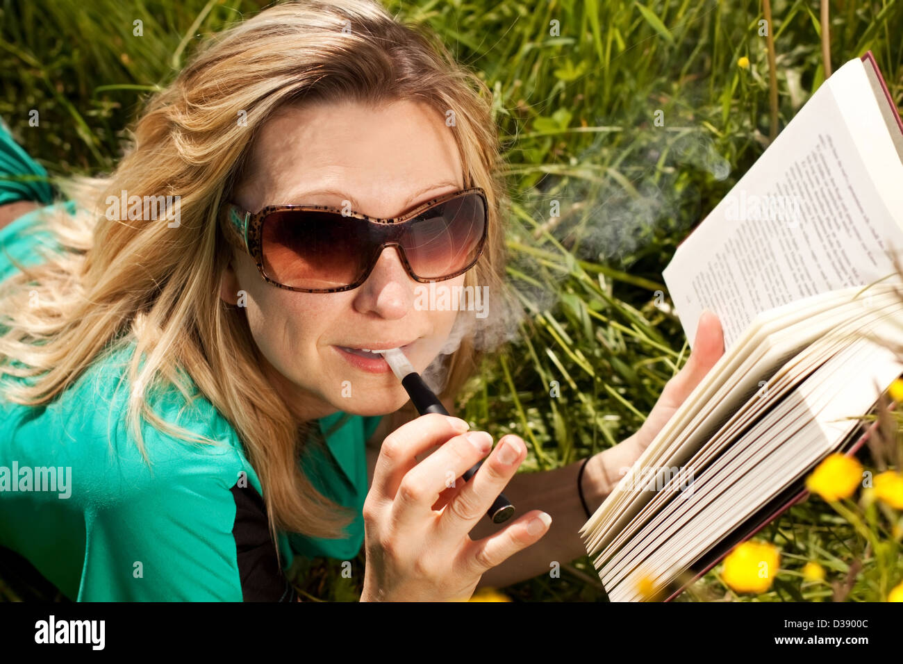 pretty blond woman reading , and evaporated to an electric cigarette - Stock Image