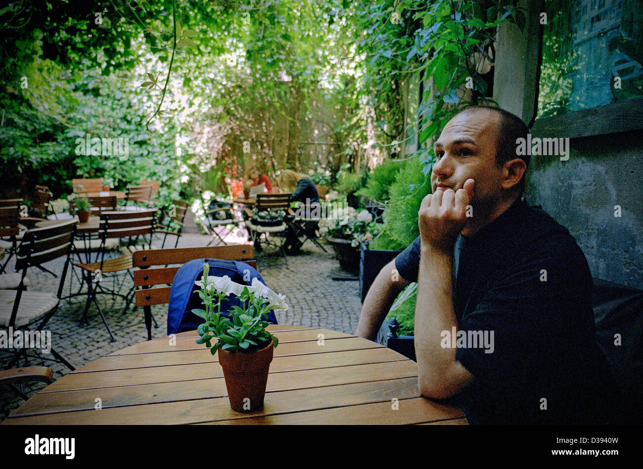 Poznan, Poland, a man sitting in the garden of a cafe and waiting Stock Photo