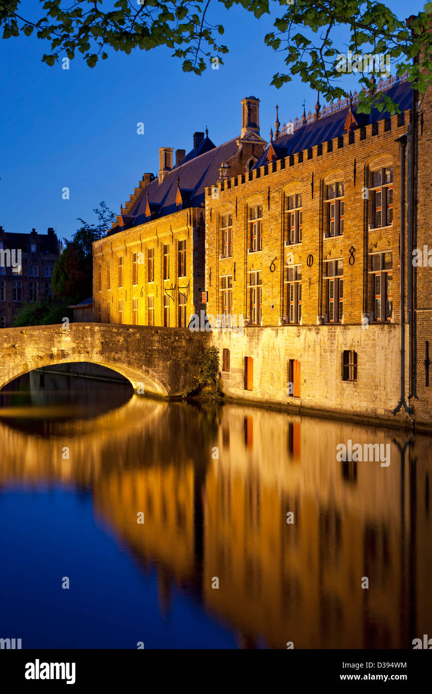 Historic buildings and bridge reflected on canal, Bruges, Belgium - Stock Image