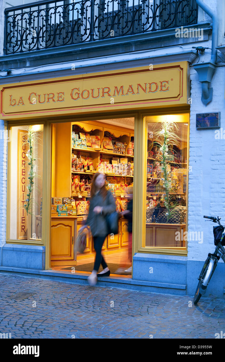 Woman stepping out of La Cure Gourmande candy store, Bruges, Belgium - Stock Image