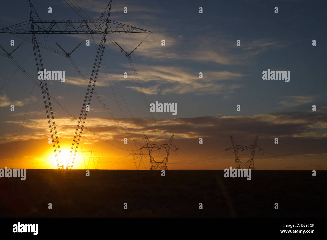 The fading sun bursts through transmission lines on the Argentine flatlands - Stock Image