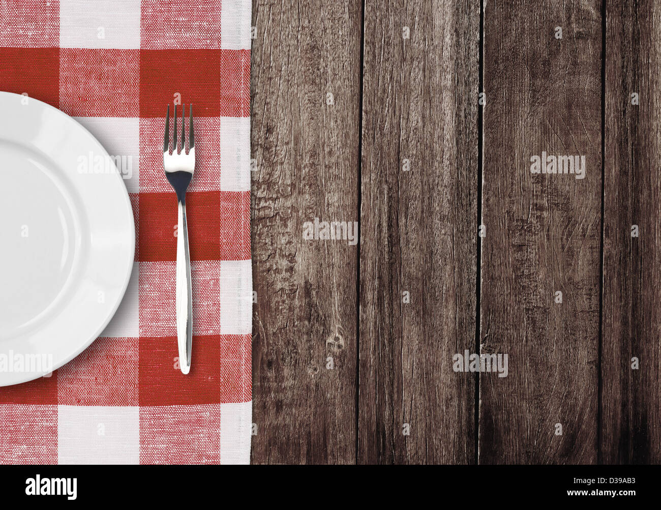white plate and fork on old wooden table with red checked tablecloth and copyspace - Stock Image