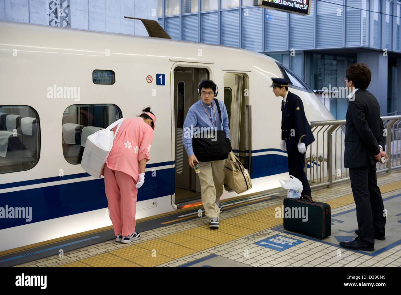 Showing respect, a cleaning woman bows to a passenger getting off a JR shinkansen bullet train at platform in Tokyo - Stock Image