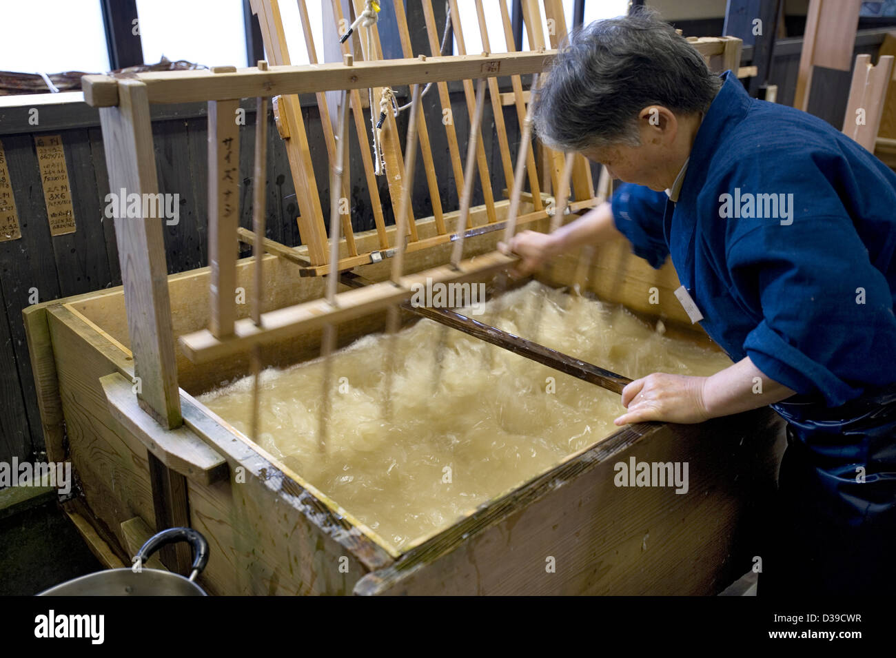 Woman using an umaguwa comb-like tool for mixing water and paper fibers by hand in a wooden tub for making traditional - Stock Image
