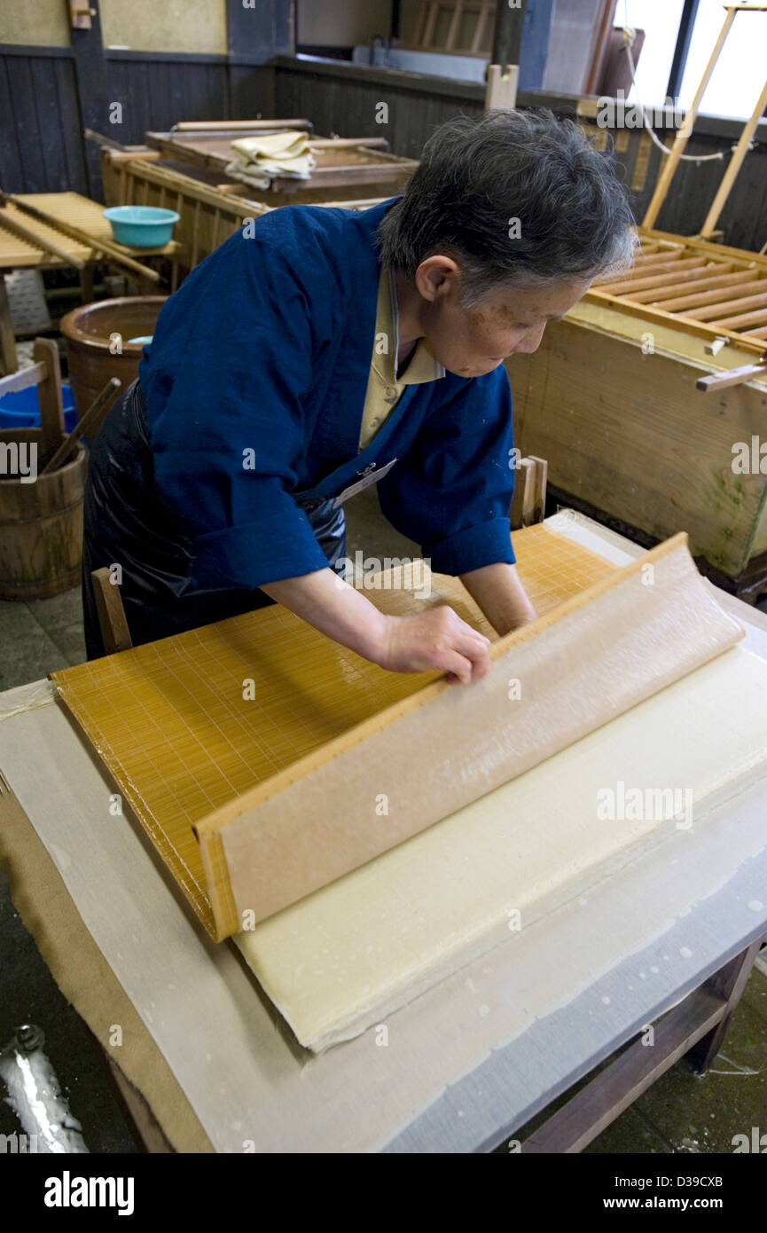 Woman making traditional washi Japanese paper by removing the su, or flexible bamboo screen, from a wet, freshly - Stock Image