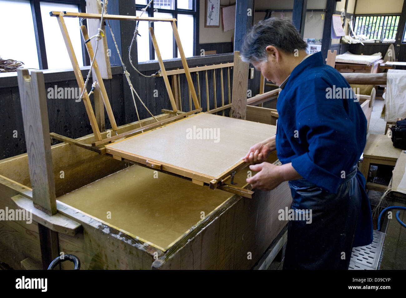 Woman removing the su, or flexible bamboo screen, used for making traditional washi Japanese paper by hand in a - Stock Image