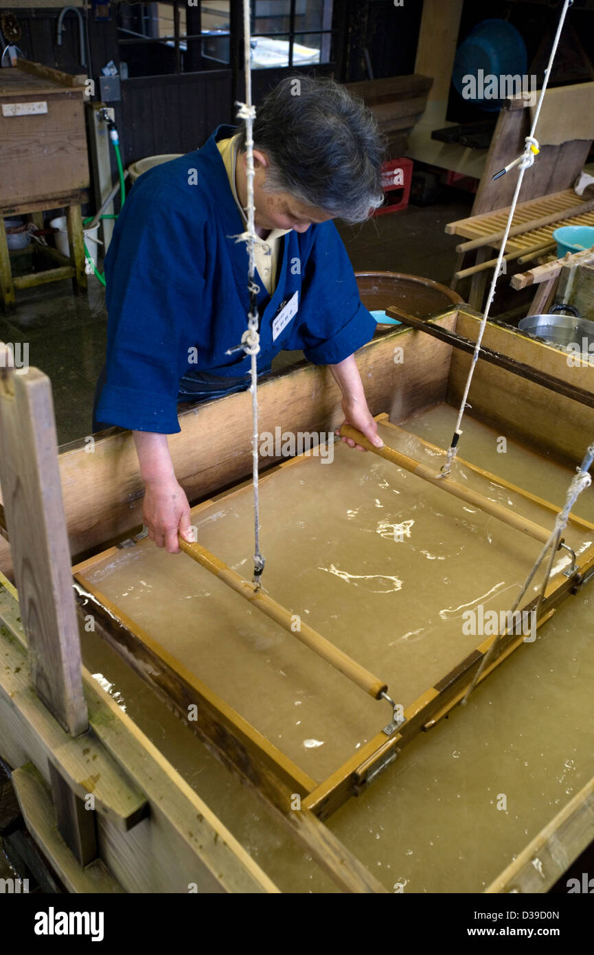 Woman making traditional washi Japanese paper by hand in a wooden tub. - Stock Image