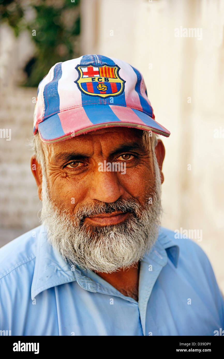 UAE Emirate of Sharjah Pakistani worker with a cap of Futbol Club Barcelona - Stock Image