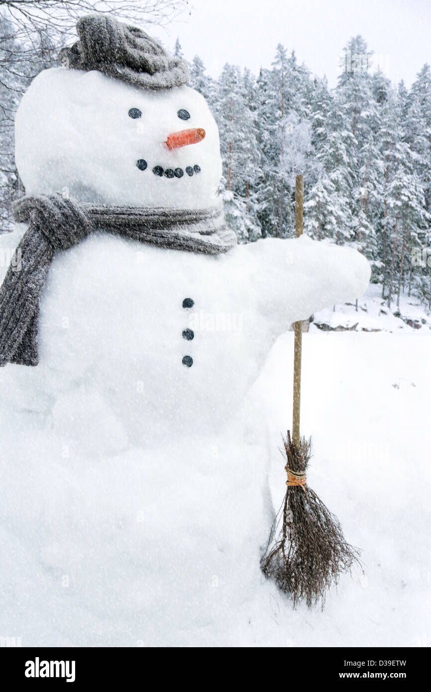 Snowman with scarf, hat and carrot nose outside in snowfall - Stock Image