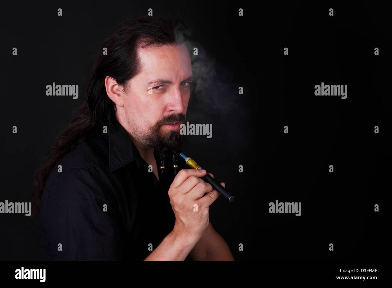 cool looking attractive man with E cigarette is point to the viewer - Stock Image