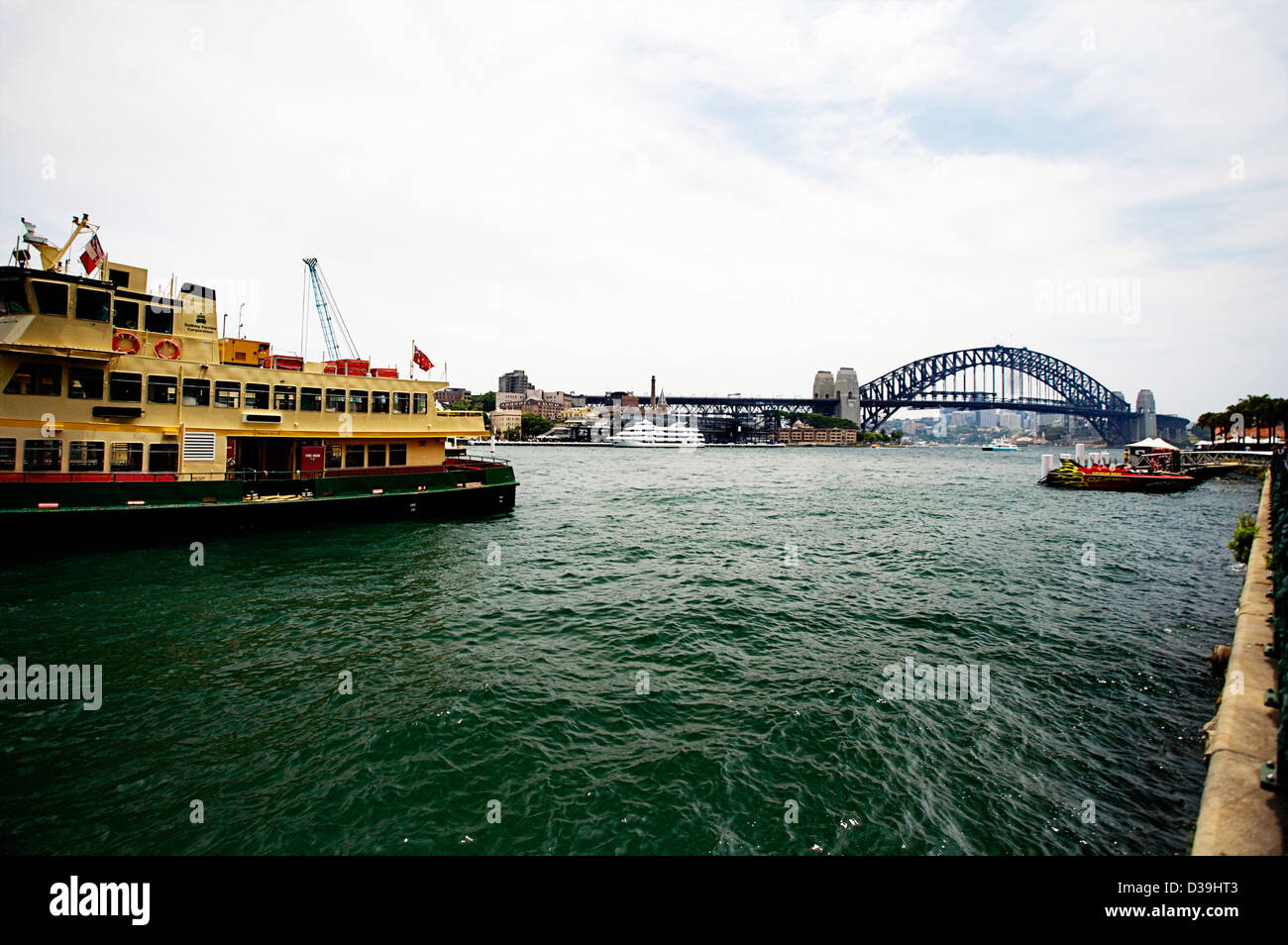 Sydney Harbor Bridge as seen from Circular Quay with a Sydney Ferry in the forefront - Stock Image