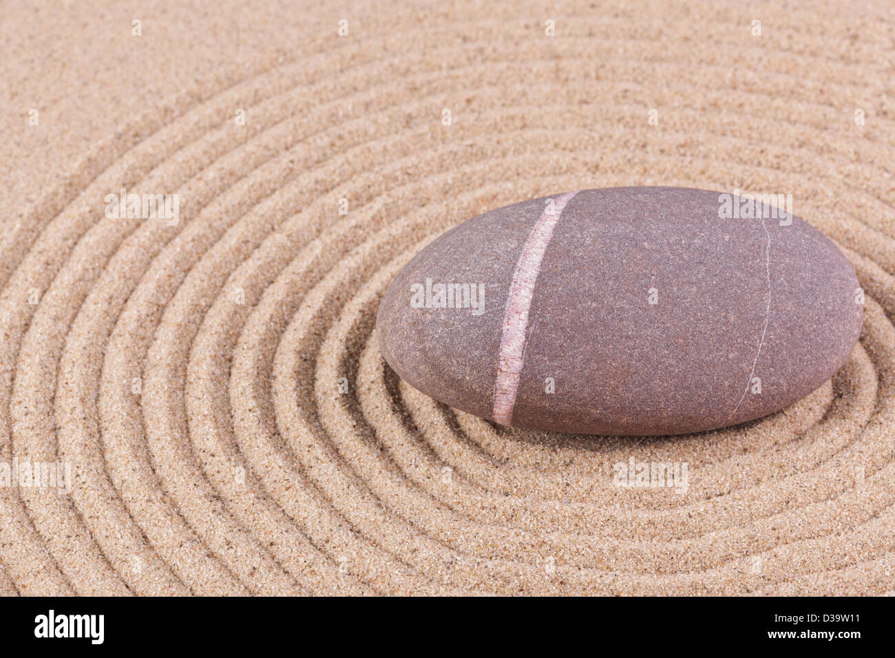 A single pebble in a raked sand circle zen garden. - Stock Image