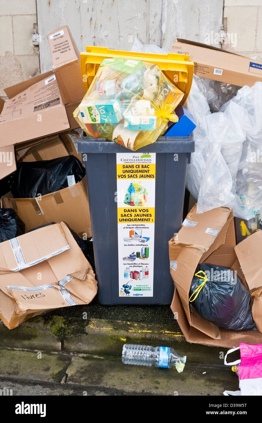 Overflowing rubbish bins awaiting collection - France. - Stock Image