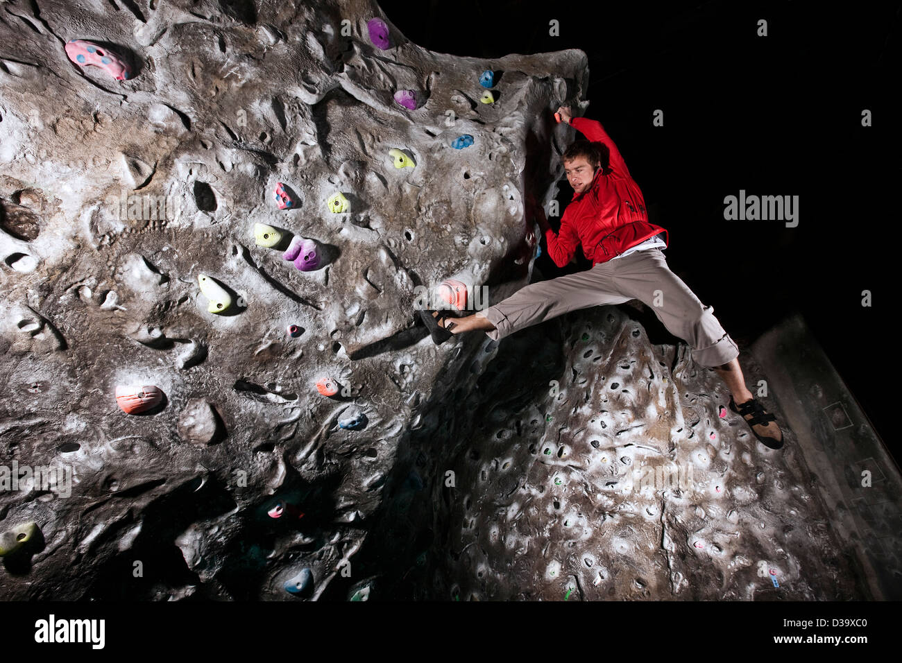 Rock climber on climbing wall, low angle - Stock Image